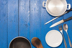 Kitchenware on the blue wooden background. Royalty Free Stock Photo