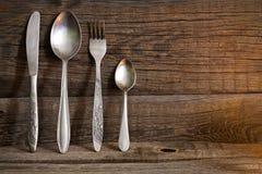 Kitchenware da cutelaria no fundo velho das placas de madeira imagem de stock