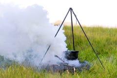 Kitchenware de acampamento - potenciômetro no fogo em uma sagacidade exterior do acampamento Fotos de Stock Royalty Free