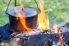 Kitchenware de acampamento - potenciômetro no fogo em um acampamento exterior Fotos de Stock
