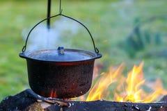 Kitchenware de acampamento - potenciômetro no fogo em um acampamento exterior Fotografia de Stock