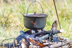 Kitchenware de acampamento - potenciômetro no fogo em um acampamento exterior Foto de Stock Royalty Free