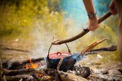 Kitchenware de acampamento - potenciômetro no fogo em um acampamento exterior Foto de Stock