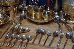 Kitchenware de bronze, colheres de bronze, forquilhas e facas no fundo de madeira da tabela imagens de stock royalty free