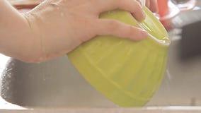 Kitchenware de lavagem da mulher sob o córrego da água filme