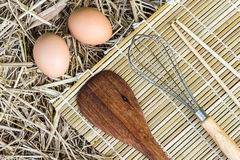 Kitchenware and eggs on straw Stock Photography