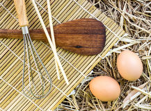 Kitchenware and eggs on straw Stock Image