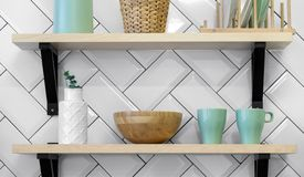 Kitchenware green cups and white vase on wooden shelves stock images