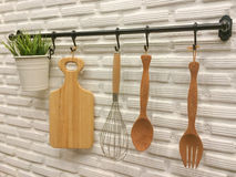 Kitchenware hanging on brick wall. Wooden kitchenware hanging on white brick wall Stock Photo