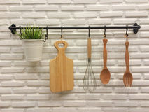 Kitchenware hanging on brick wall. Wooden kitchenware hanging on white brick wall Royalty Free Stock Photo