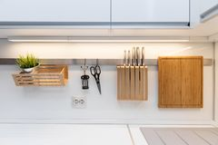 Kitchenware hanging on the rail in the white glossy kitchen Stock Images