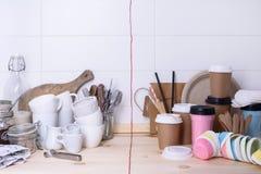 Kitchenware keramiskt och pappers- för på gå kuper, på trätabletopen, vit bakgrund Royaltyfri Foto