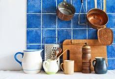 Kitchenware naczynia barwione garnków dzbanków niecki, tnąca deska, drewniana łyżka, bednarz kopyść stewpan taflujący tła błękit Zdjęcie Royalty Free