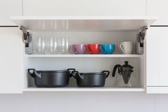 Kitchenware. Opened cupboard with kitchenware inside royalty free stock photo