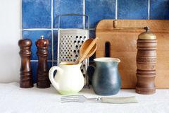 Kitchenware retro utensil set. Old style interior objects. Pitchers grater cutting board and fork. Blue tiled background Royalty Free Stock Photos