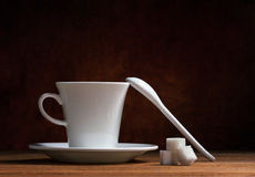 Kitchenware and sugar. White ceramic coffee cup on saucer, ceramic spoon and cubes sugar on wooden table on dark brown background Royalty Free Stock Images