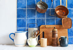 Kitchenware utensils. colored pots jugs pans, cutting board, wooden spoon, cooper ladle stewpan. blue tiled background Royalty Free Stock Photo