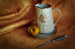 Kitchenware for villagers. Nutrmort with jugs, an apple and a knife. Warm fabric background. Autumn tones. Rustic style royalty free stock photography