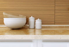 Kitchenware on the worktop. Ceramic and glass kitchenware on the marble worktop in front of modern wooden wall. White kitchen design Stock Photo