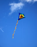 Kite. A funny flying kite with a smiling sun face. Blue sky. Image with copy space stock image
