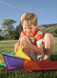 Kite 2. Little caucasian boy smiling while building a colorful kite at an outdoor park Royalty Free Stock Photos