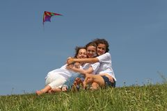 Kite. Three embracing girls on a green grass with a flying kite on a background Stock Photos