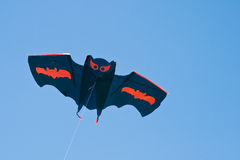 Kite. Image showing a flying kite in shape of a black bat with orange signs Stock Photos