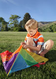 Kite. Young Caucasian boy assembling a kite at a park Stock Images