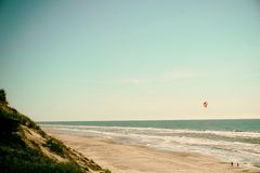 Kite above waves on beach Royalty Free Stock Photography