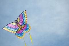 Kite airborne in the sky. Multi-colored kite flies against a blue sky background with cloud wisps, with yellow streamers trailing behind Stock Photography