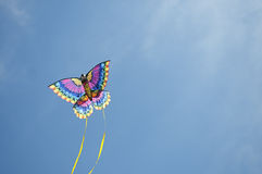 Kite arcing through the sky. Multi-colored kite flies against a blue sky background Stock Images