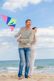 Kite blow. Happy winter relaxing couple on the coast running kite dragon stock image
