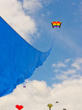 Kite with a blue ribbon flying high Royalty Free Stock Image
