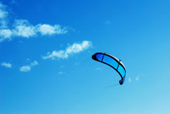 Kite in the blue sky. Big blue kite in the blue sky with some clouds royalty free stock photography
