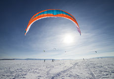 Kite boarders in snowy landscape. Scenic view of kite boarders in snowy landscape with blue sky background stock images
