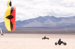 Kite Buggying. Two kite buggy pilots ride across a dry lakebed Royalty Free Stock Images