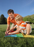 Kite Building. Young white father helping son assemble a kite outdoors Royalty Free Stock Photo