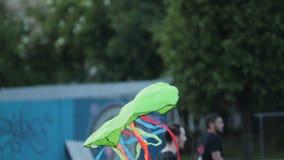 Kite with cartoon eyes flies and falls down onto lush grass