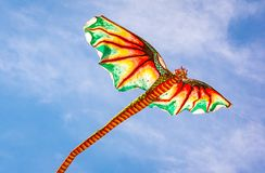 Kite with a dragon head flying in the wind. Indonesian kite with an ugly dragon head and a long tail flying in the wind, Sanur, Bali, Indonesia, April 21, 2018 Stock Photos