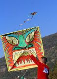 Kite festival - a guy with big square kite painted as a monster head royalty free stock photography