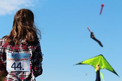 Kite festival - youg girl watching kites in the sky stock images