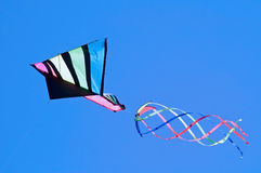 Kite in Flight. Colorful kite in flight against a blue sky royalty free stock photos