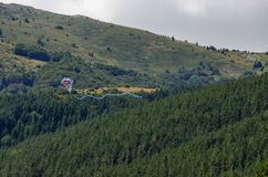 Kite fly high over panorama of glade and green forest. In Vitosha mountain, Bulgaria stock photo