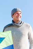 Kite fly man. Smiling happy healthy man walking on beach with kite in winter autumn spring time stock photo