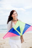 Kite fly woman. Smiling happy healthy woman walking on beach with kite in winter autumn spring time stock photo