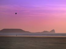 Kite flying. Man flying kite on a deserted beach at sunset royalty free stock photography