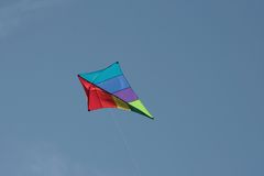 Kite Flying. A colorful diamond shaped kite flying in a clear blue sky Royalty Free Stock Photo