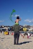 Kite Flying. Little girl on parents shoulders flying a kite with back to camera, Bondi Beach, Australia Stock Image