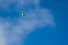 Kite flying against blue sky and light clouds Stock Photography