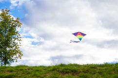 Kite flying in the air. Entertainment for children and adults in free time. Collect the kite. Kite flying in the air. Beautiful sky with clouds on background Stock Photography